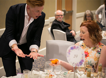 Magician Matt Gore performing walk around close up magic for a guest at a wedding