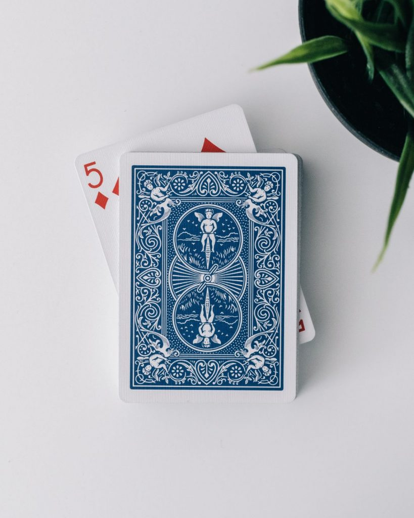 deck of playing cards with 5 of diamonds sticking out